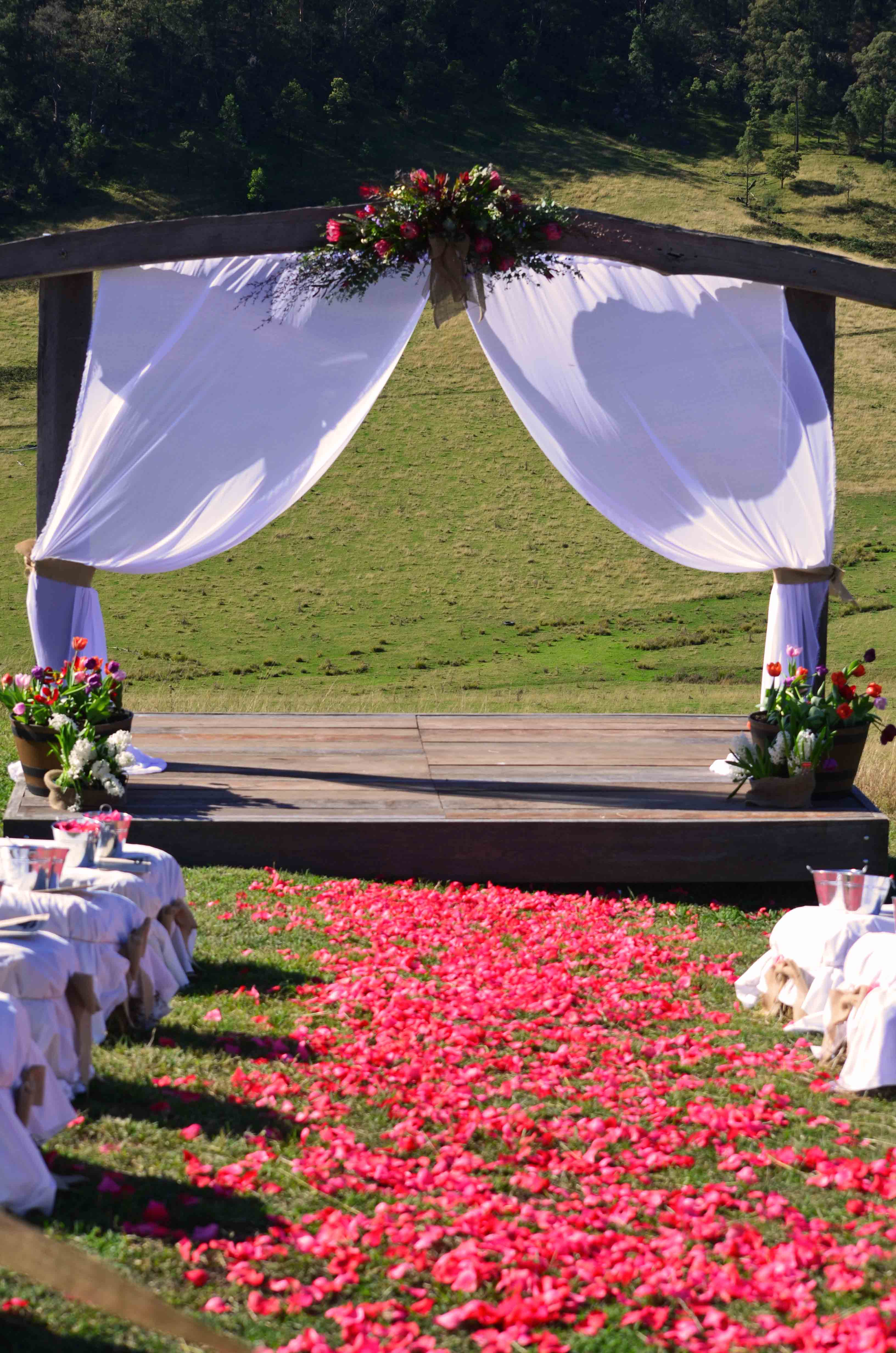 Country australian wedding venue near sydney chapman valley red rose petals leading to a rustic timber stage and archway junglespirit Images