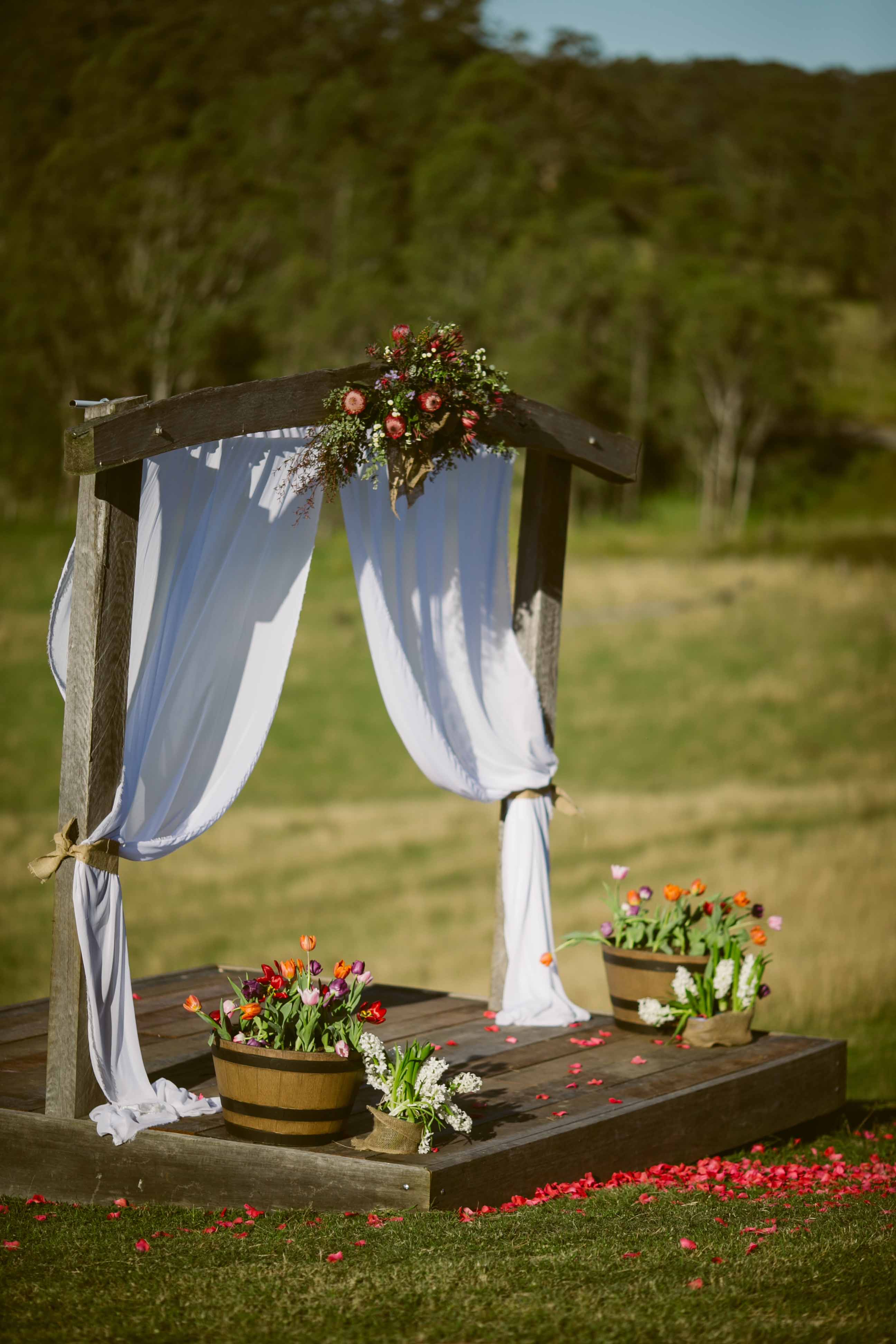 Country australian wedding venue near sydney chapman valley the rustic timber archway decorated with bright coloured flowers and beautiful white flowing chiffon junglespirit Images